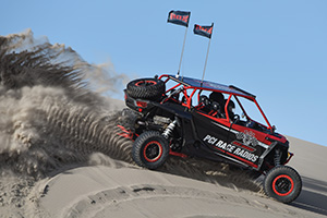 ATVs playing in the sand dunes. Courtesy of PCI  Race Radios.